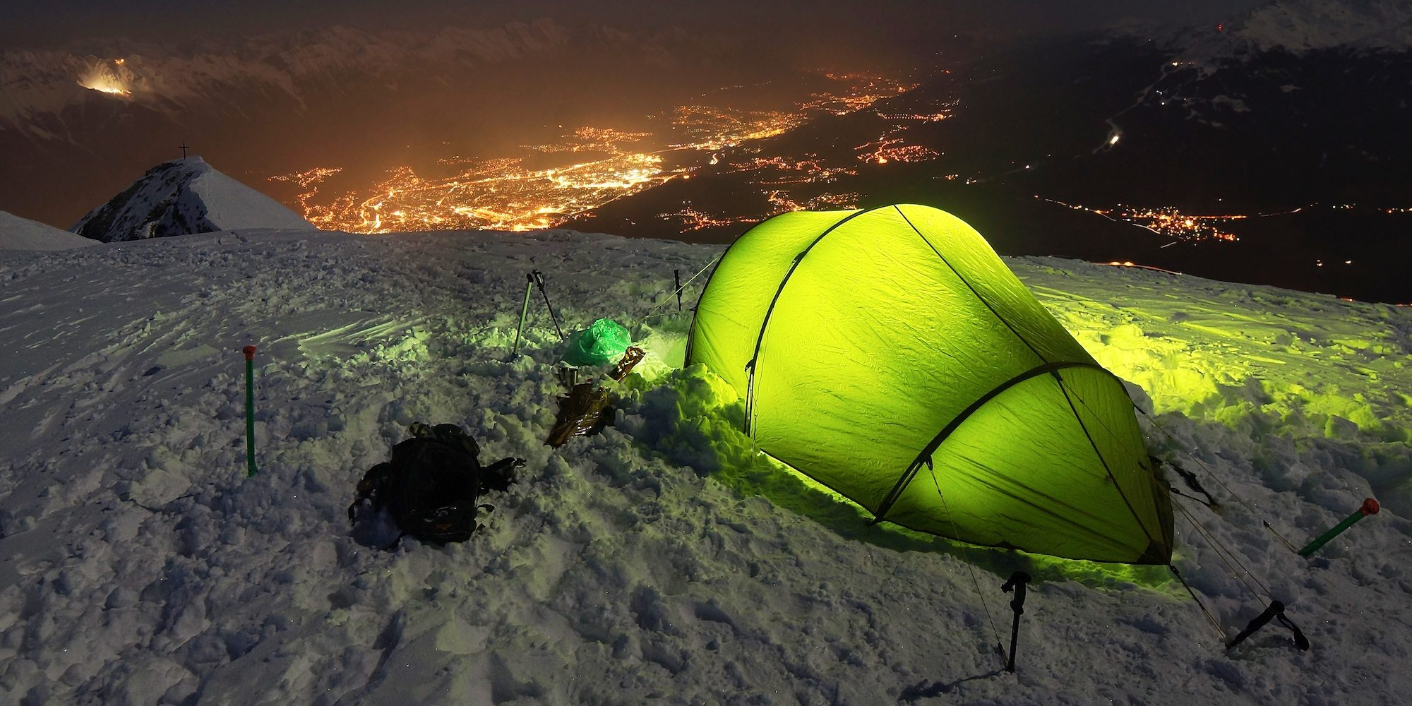 Illuminated green tent on snowy mountain at night with city lights in the background