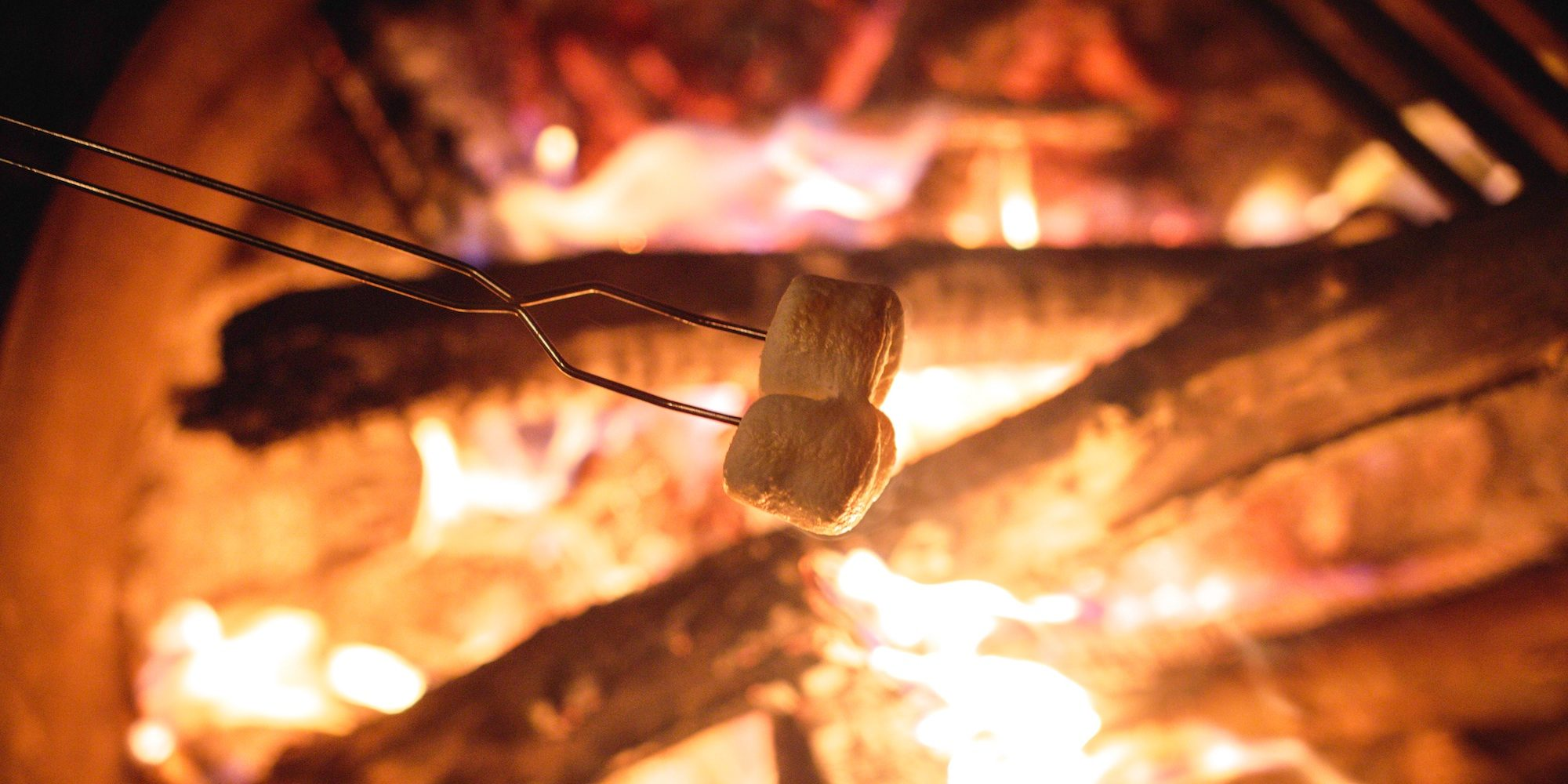Two marshmallows on hanger being roasted over a campfire