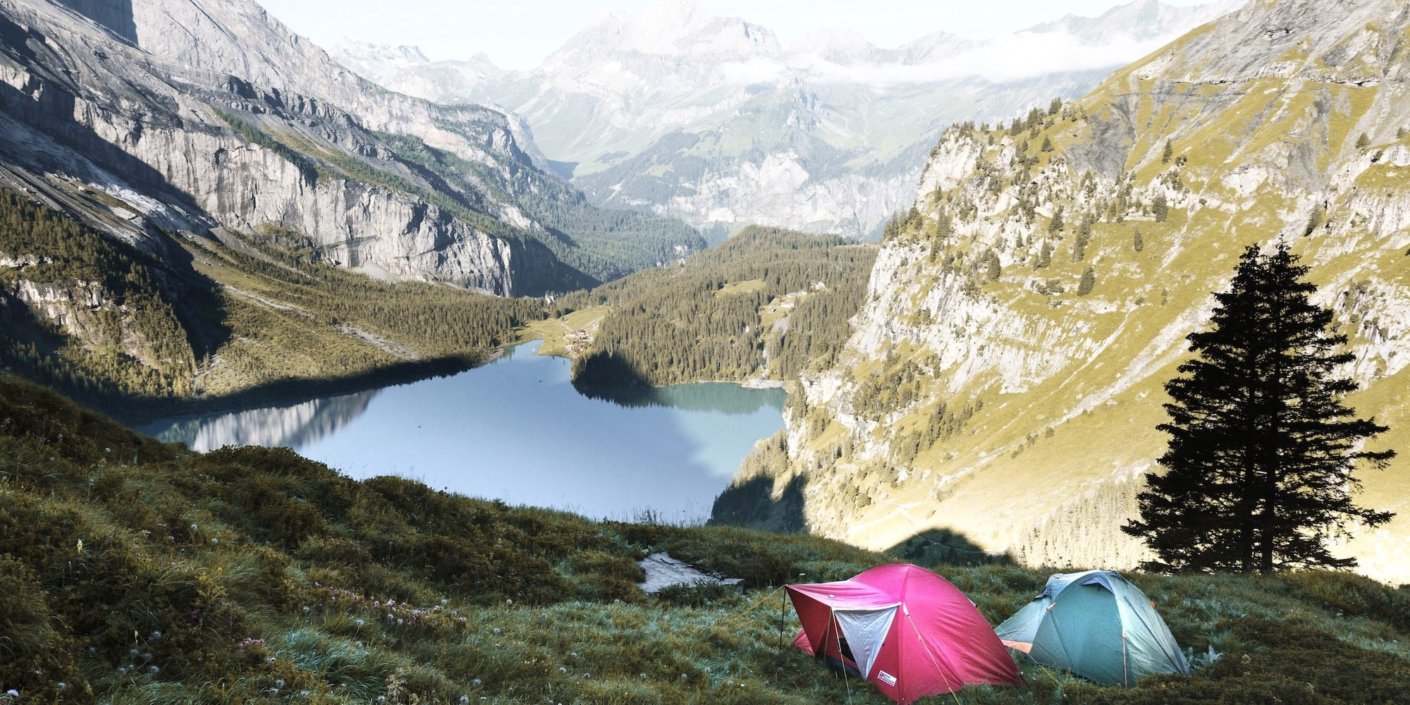 Pink & green tent in a valley between mountains with a lake in the background